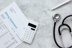 opieki zdrowotnej fakturowania oświadczenie z lekarki piórem na kamiennego tła odgórnym widoku i stetoskopem obraz royalty free