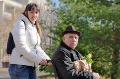 Opiekun pomaga mężczyzna w wózku inwalidzkim Zdjęcia Stock