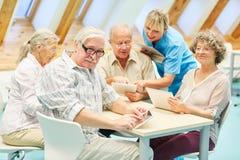 Opiekun pomaga seniorów w komputerowym kursie obrazy stock