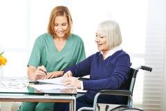 Opiekun pomaga starszej kobiety z kontraktami obraz stock