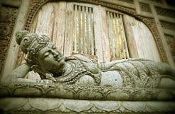 Opierający Buddha balijczyka religijną statuę w Ubud w wyspie Bali i śpiący, Indonezja przy bramą świątynia w Buddhis obrazy stock