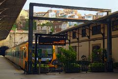 Opinión del paisaje del sao viejo Bento del ferrocarril de Oporto con el tren amarillo típico cerca de la plataforma imagen de archivo