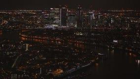 Opinião aérea da noite de arranha-céus iluminados no distrito financeiro de Canary Wharf e zona oriental de Londres ao lado do ri video estoque