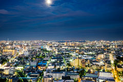 Opinião aérea da noite do olho moderno panorâmico do pássaro da skyline da cidade sob o fulgor de néon dramático e obscuridade bo Fotografia de Stock