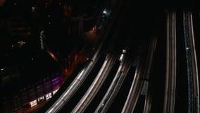 Opinião aérea da noite no estação de caminhos de ferro, trens que movem-se lentamente das plataformas filme