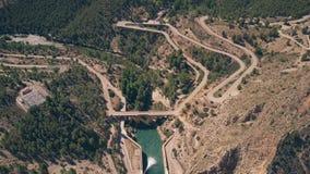 Opinião aérea da pena da estrada e da represa hairpinned ventosas do carro nas montanhas na Espanha vídeos de arquivo