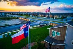 Opinião aérea do zangão ao lado da bandeira americana e do Texas Flag que voam altamente acima dos desenvolvimentos modernos de S imagens de stock royalty free
