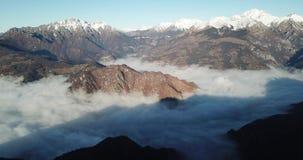 Opinião aérea do zangão aos cumes de Orobie Neve fresca nas montanhas A névoa cobre o vale e as vilas Panorama de Farno vídeos de arquivo