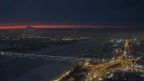 Opinião aérea do zangão do banco de rio da cidade coberto de neve da noite com engarrafamentos filme