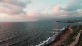Opinião aérea do zangão da praia rochosa com o cais pedestre pequeno e ondas grandes que colidem em penhascos filme