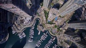 Opinião aérea do zangão de Emiratos Árabes Unidos do porto do porto de Dubai com construções do iate e do arranha-céus do barco n filme