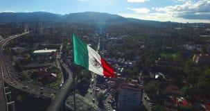 Opinião aérea do zangão de uma bandeira mexicana enorme que acena na vista panorâmica traseira alguns subúrbios e montanhas Os ca