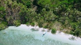 opinião aérea do zangão 4k da praia isolada remota do paraíso com as palmeiras que balançam no vento Barco de Banka em azuis cele vídeos de arquivo