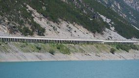 Opinião aérea do zangão do lago Livigno um lago artificial alpino e a estrada protegidos por avalanchas Cumes italianos Italy imagens de stock royalty free