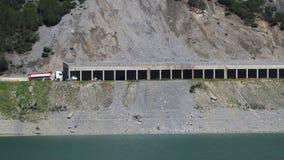 Opinião aérea do zangão do lago Livigno um lago artificial alpino e a estrada protegidos por avalanchas Cumes italianos Italy imagens de stock