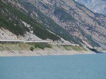 Opinião aérea do zangão do lago Livigno um lago artificial alpino e a estrada protegidos por avalanchas Cumes italianos Italy imagem de stock royalty free