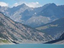 Opinião aérea do zangão do lago Livigno um lago artificial alpino e a estrada protegidos por avalanchas Cumes italianos Italy fotos de stock