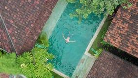 Opinião aérea do zangão o homem novo que flutua sobre a piscina azul que aprecia o banho de sol e as férias em tropical video estoque
