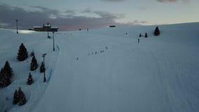 Opinião aérea do zangão os esquiadores na inclinação, esqui da noite na estância de esqui de Monte Pora vídeos de arquivo