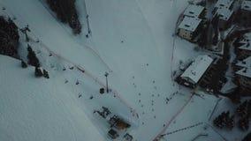 Opinião aérea do zangão os esquiadores na inclinação, esqui da noite na estância de esqui de Monte Pora filme