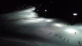 Opinião aérea do zangão os esquiadores na inclinação, esqui da noite na estância de esqui de Monte Pora