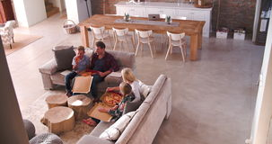 Opinião aérea a família que senta-se em Sofa Eating Pizza filme