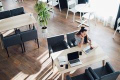 Opinião aérea a jovem mulher que verifica o tempo em seu smartwatch ao trabalhar em seu portátil em um café Vista superior dispar Fotografia de Stock Royalty Free