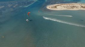 Opinião aérea maravilhosa do zangão 4k nos surfistas profissionais que kiteboarding no oceano azul claro no seascape tropical do  filme