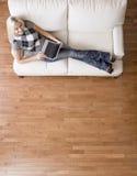 Opinião aérea a mulher no sofá com portátil imagem de stock royalty free