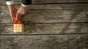 Opinião aérea o corretor de imóveis ou o arquiteto que colocam um telhado de papel, fina imagem de stock
