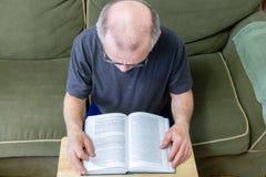 Opinião aérea o homem calvo que lê um livro fotografia de stock royalty free