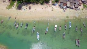 Opinião aérea o pescador Village com muitos barcos de pesca tradicionais entrados pela costa de mar em Tailândia filme