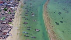 Opinião aérea o pescador Village com muitos barcos de pesca tradicionais entrados pela costa de mar em Tailândia video estoque