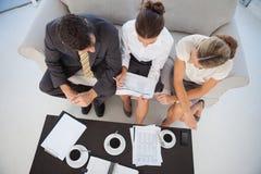 Opinião aérea os colegas que trabalham e que comem o café junto Foto de Stock Royalty Free