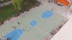 Opinião aérea os desportistas que jogam o basquetebol no sportsground do parque vídeos de arquivo
