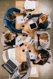 opinião aérea os empresários no encontro na tabela com os copos de café digitais dos dispositivos foto de stock royalty free