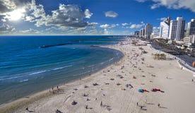 Opinião aérea os povos que banham-se no sol, na praia de Tel Aviv surfista do papagaio que desliza através do oceano azul, Israel fotografia de stock