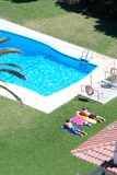 Opinião aérea os povos que sunbathing por uma piscina Imagem de Stock Royalty Free