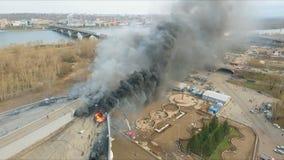 A opinião aérea os sapadores-bombeiros corajosos que arriscam suas vidas extingue um grande fogo no telhado da construção video estoque