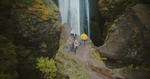Opinião aérea os turistas na cachoeira de Gljufrabui em Islândia Helicóptero que move-se longe dos amigos, selfie no zangão filme