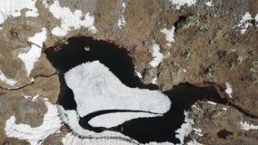 Opinião aérea superior e para baixo do zangão de um lago natural alpino durante a estação de mola Derretimento da neve Cumes ital filme
