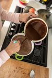Opinião aérea um cozinheiro que esvazia o molho de chocolate de um potenciômetro imagem de stock