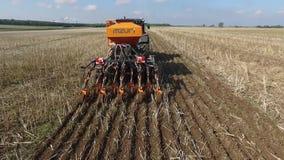 A opinião aérea um fazendeiro está semeando o milho em um campo enorme, Polônia, 06,2017 filme