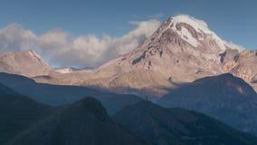 Opinião alpina da paisagem da montanha de Kazbek coberta com a neve, igreja antiga dos desfiladeiros no monte filme