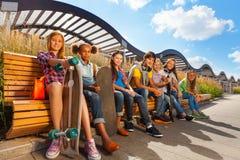 Opinião as crianças felizes que se sentam no banco de madeira Foto de Stock