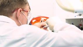 Opinião ascendente próxima o dentista em luvas do látex que examina a mulher com boca aberta, conceito dos cuidados dentários med fotografia de stock royalty free