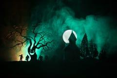 Opinião assustador os zombis na árvore inoperante do cemitério, na lua, na igreja e no céu nebuloso assustador com névoa, conceit imagem de stock royalty free