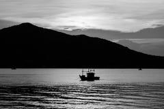 Opinião bonita do seascape da imagem preto e branco abstrata do barco de pesca da silhueta que flutua no mar fotografia de stock