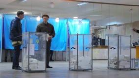 A opinião borrada o eleitor fêmea louro de Yong no revestimento vermelho obtém a cédula na mesa de voto no presidente da eleição  filme