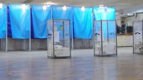 A opinião borrada o eleitor fêmea louro de Yong no revestimento vermelho obtém a cédula na mesa de voto no presidente da eleição  video estoque